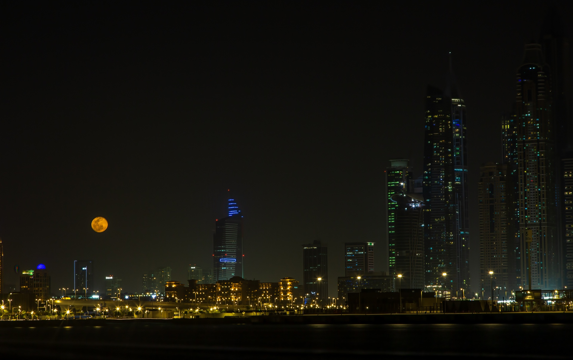Rising moon over cityscape